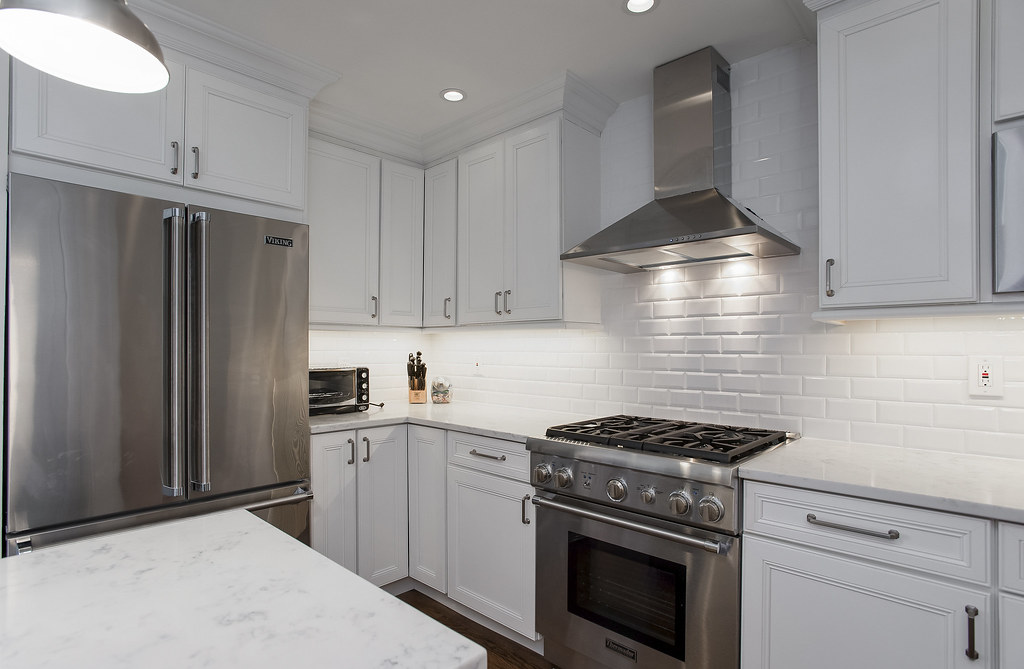 Golden and silver elements in a white kitchen design