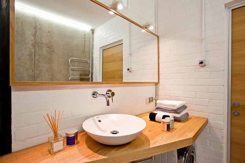 Белая минималистичная ванная комната и кирпичная стена